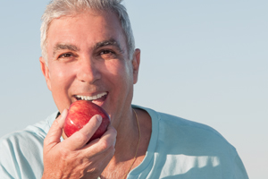Man with Dentures Eating an Apple